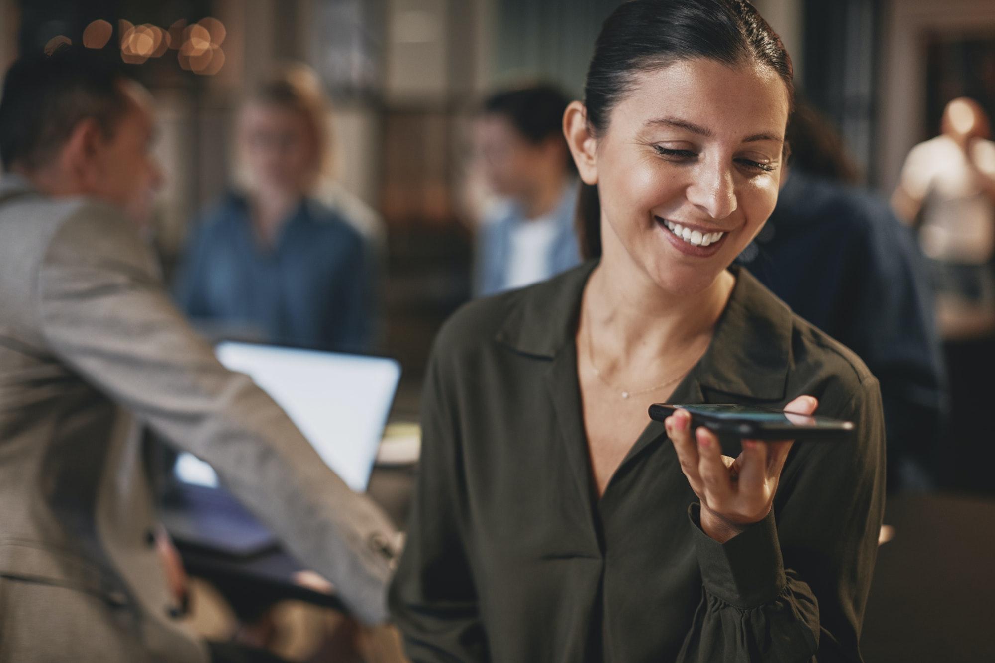 Smiling businesswoman talking on speakerphone in an office